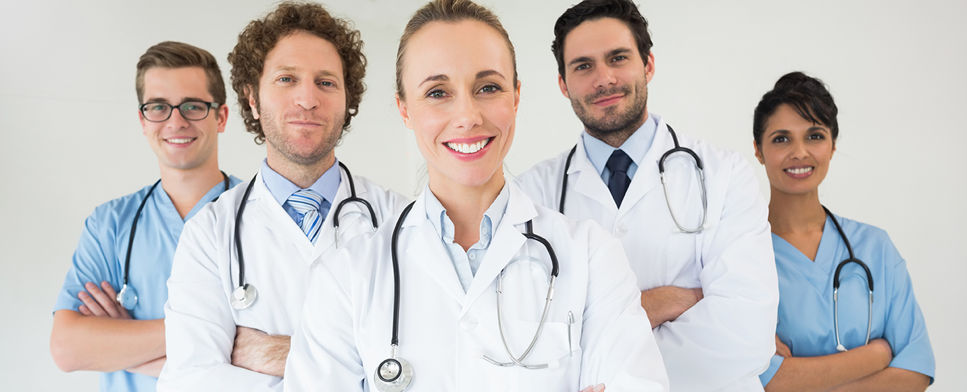 Portrait of happy medical team standing together in hospital
